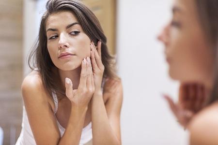девушка у зеркала ищет проблемные места на коже лица