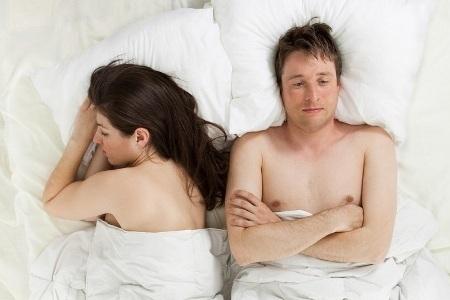 задумавшийся мужчина в постели рядом с женщиной